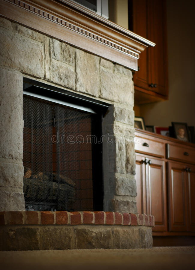 Fireplace Mantel. Stone and brick fireplace with wooden mantel royalty free stock photography
