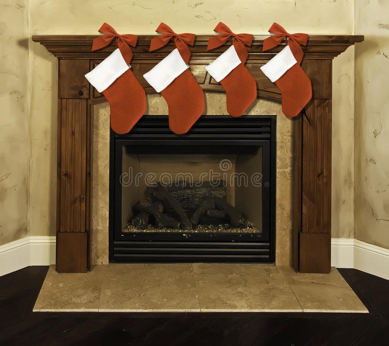 Fireplace mantel Christmas stockings. Four red Christmas stockings with bows hanging on fireplace mantel royalty free stock photography