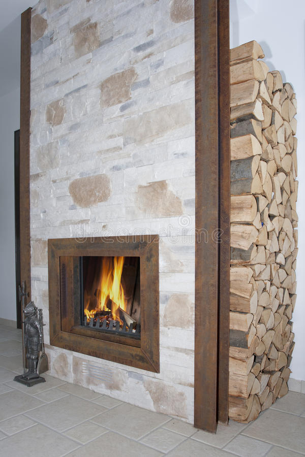 Photo about Fireplace in metal frame and stone wall. Image of reflect