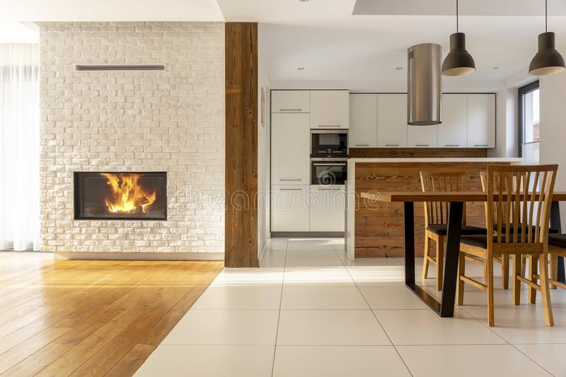 Fireplace in spacious white house interior with wooden chairs at stock images
