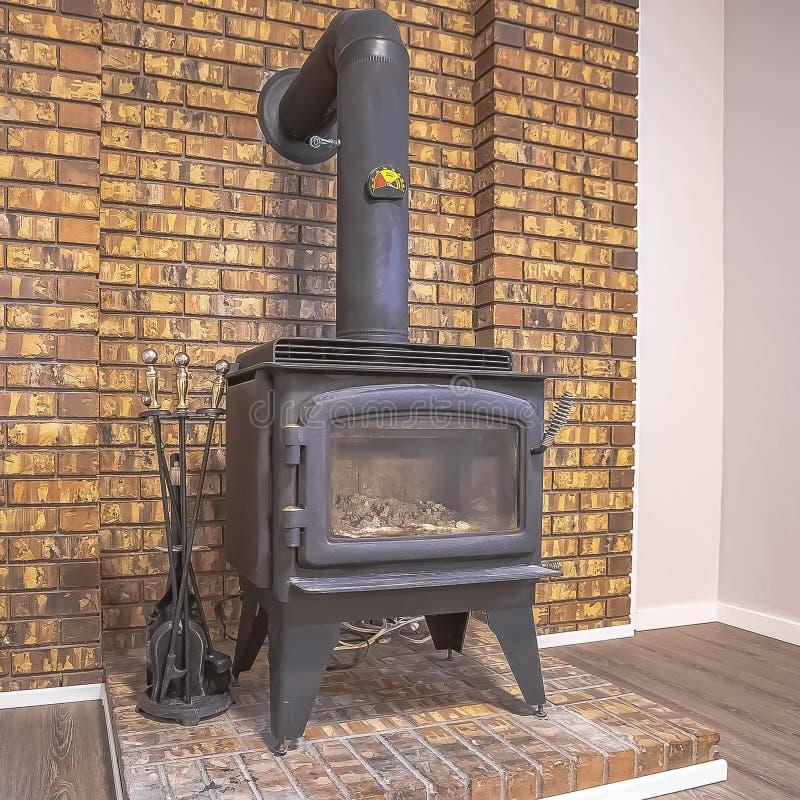 Fireplave en métal de noir de place avec la porte en verre et tuyau installé contre un mur de briques photo stock