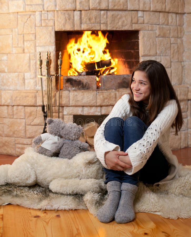 Fireside de assento do adolescente feliz foto de stock