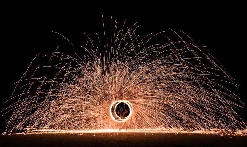 Firestarter exécutant l'exposition étonnante du feu avec des étincelles la nuit images stock