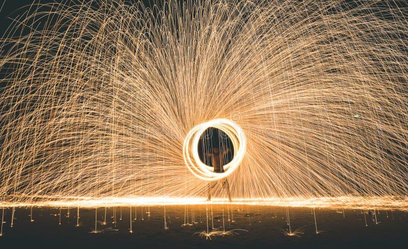 Firestarter que executa a mostra de surpresa do fogo com os sparkles na noite - festival do evento do partido da Lua cheia na vid fotografia de stock royalty free