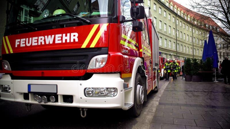 Firetruck in het Duits, brandbestrijders op achtergrond, brand en hulpdiensten royalty-vrije stock afbeelding