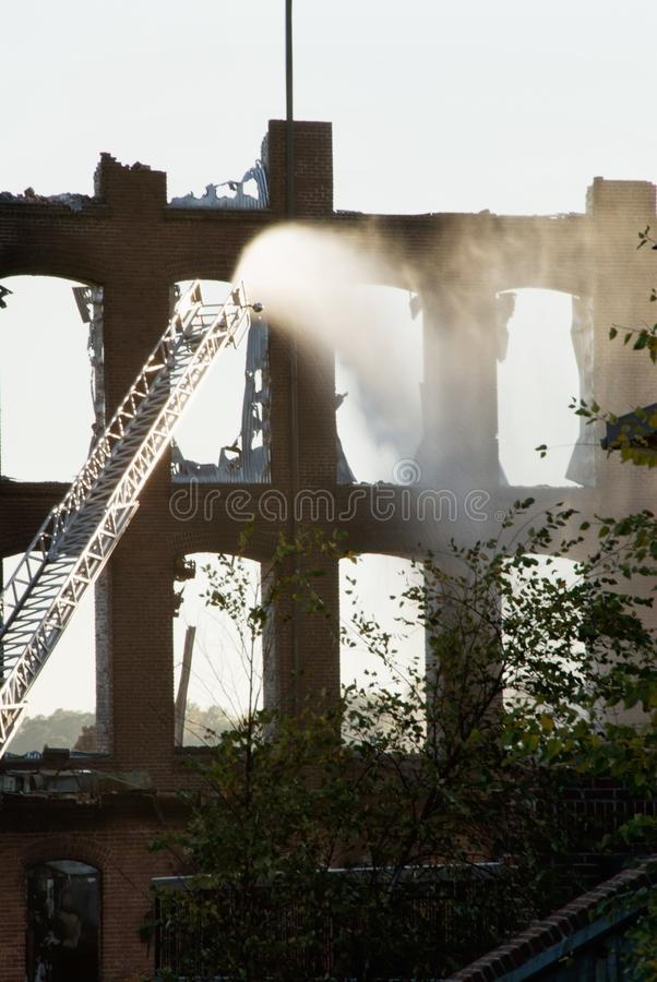 Firetruck Ladder Shooting Water into a Burning Building stock photo