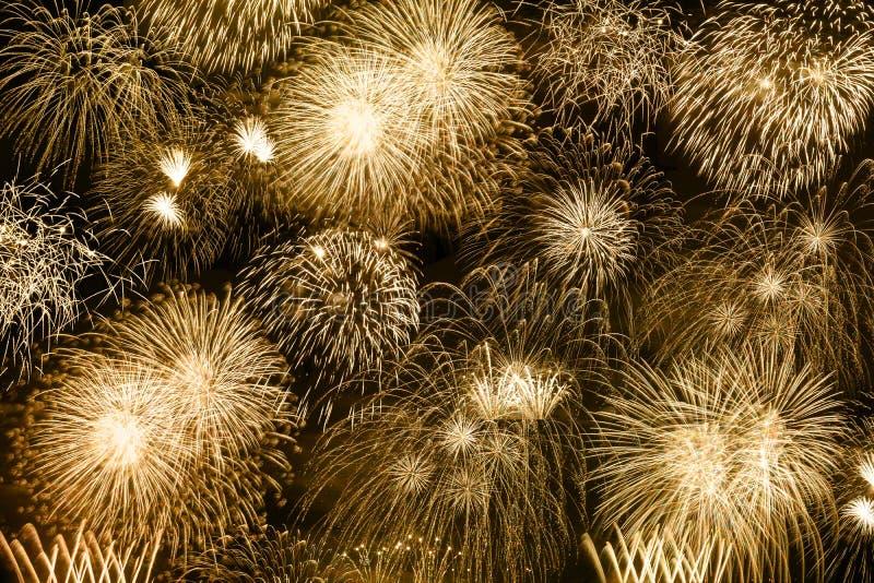 Firew dorato di anno di anni del fondo dell'oro dei fuochi d'artificio di notte di San Silvestro fotografia stock