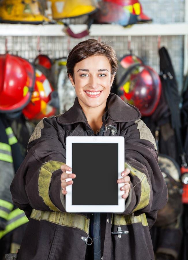 Firewoman que mostra a tabuleta de Digitas no quartel dos bombeiros foto de stock