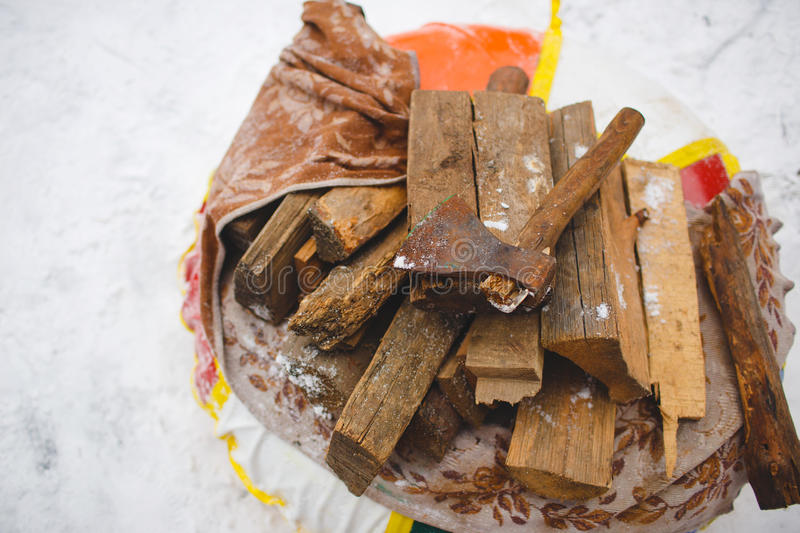 Firewood and axe on snow. Chopping wood royalty free stock photo