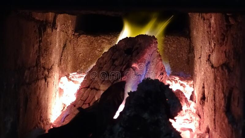 Firewood burns in the stove. Tongues of flame play with bright multi-colored paints, coals fill the firebox with red flowers. royalty free stock image