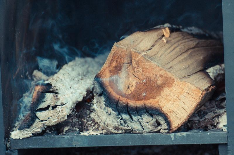 Firewood, carbon and ash in fireplace or smokehouse. Burning firewood, carbon and ash in fireplace or smokehouse stock image