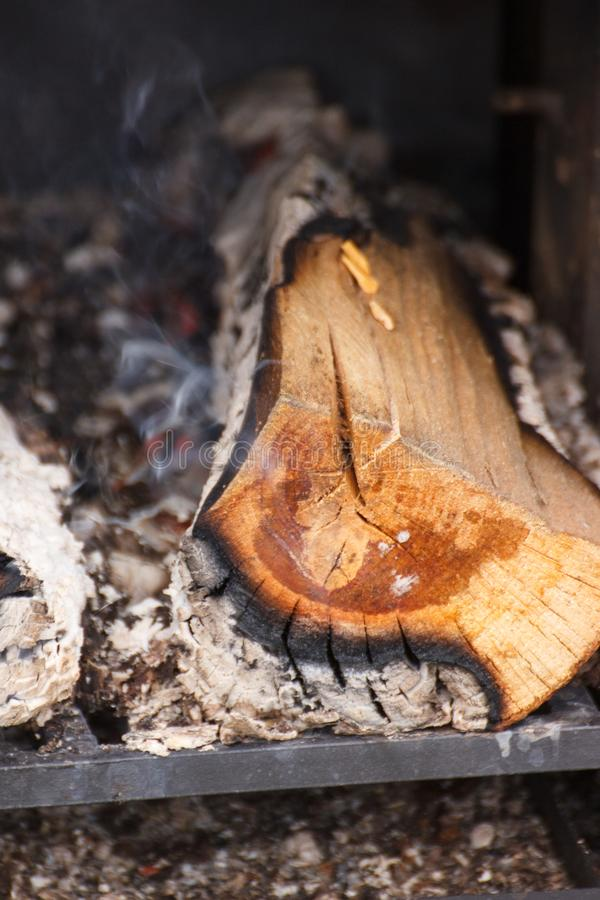 Firewood, carbon and ash in fireplace or smokehouse. Burning firewood, carbon and ash in fireplace or smokehouse royalty free stock images