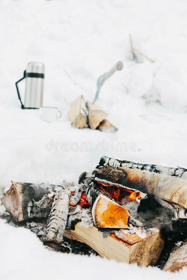 Firewood with coals in the fire in the snow on the background of thermos and hatchet. Travel concept stock photo