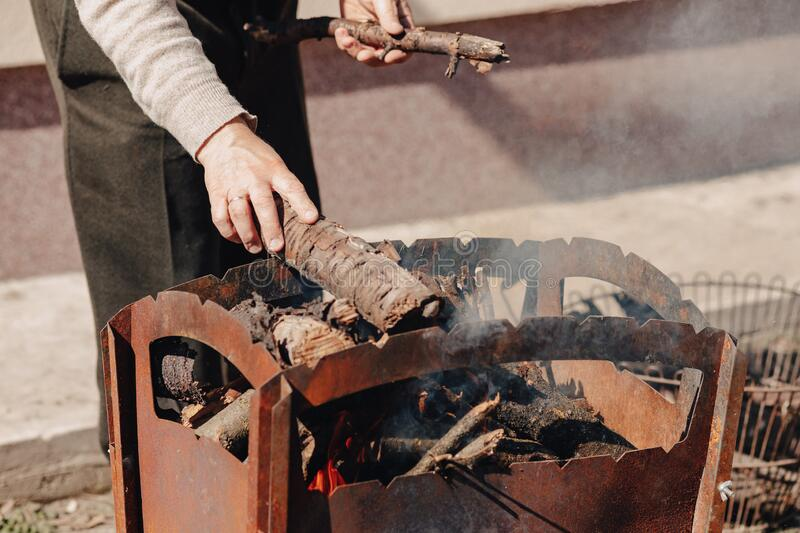Firewood in the grill. man fires bonfire for grilling meat. Nature food preparation royalty free stock image