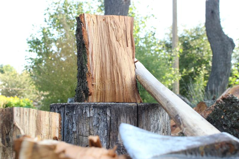 Firewood and heavy axe on wood block. stock photography