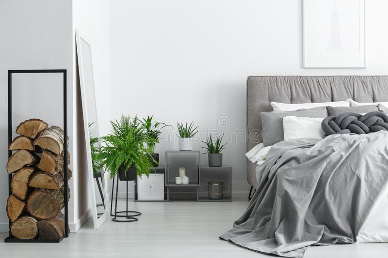 Firewood next to mirror. Firewood next to a mirror in an elegant, and cozy modern, monochromatic bedroom interior stock photos