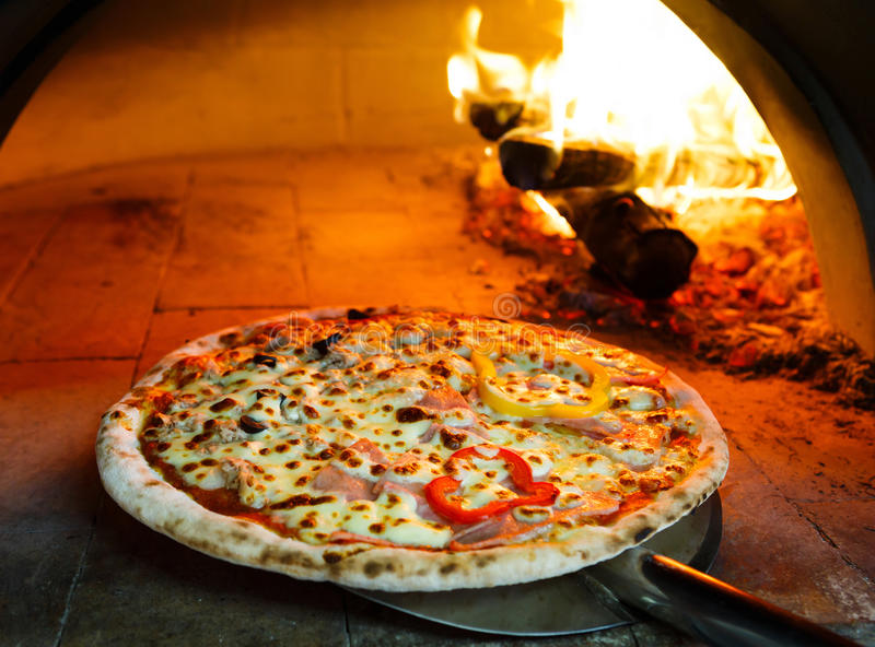 Firewood oven pizza. Close up pizza in firewood oven with flame behind royalty free stock images