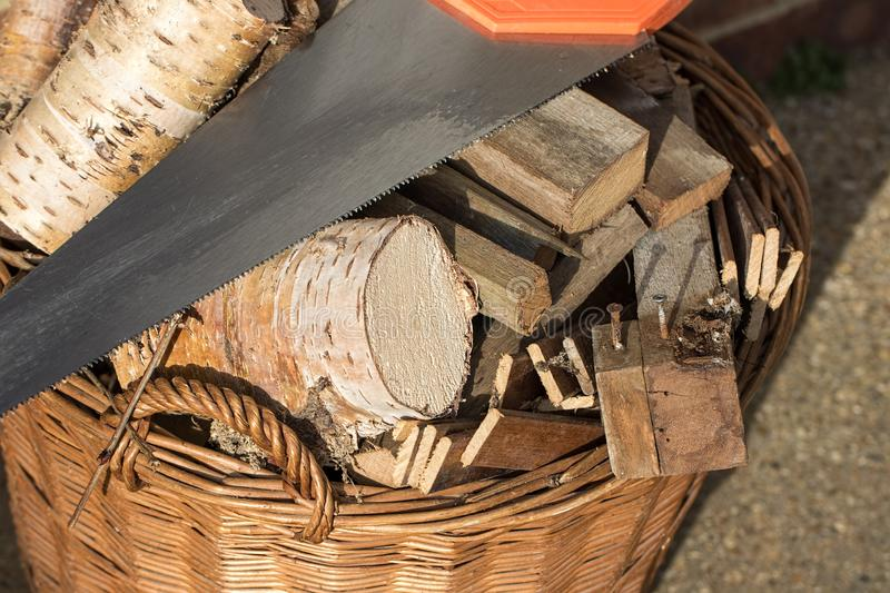 Firewood. Preparing for winter. Sawn logs and old wood fuel with saw. Firewood. Preparing for Winter. Assortment of sawn logs and old wood fuel with saw. Basket stock photos