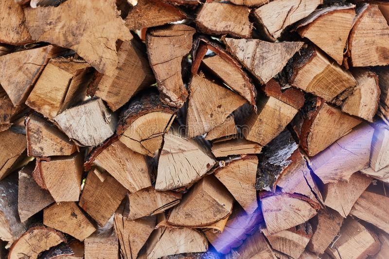 Firewood round stacked under the wall. A pile of wooden logs. Wooden logs pattern backdrop royalty free stock photography
