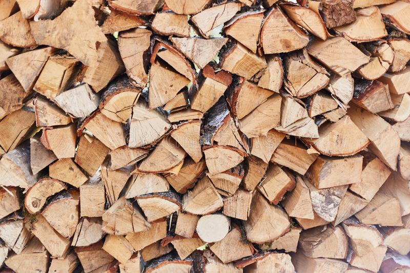 Firewood round stacked under the wall. A pile of wooden logs. Wooden logs pattern backdrop stock photography