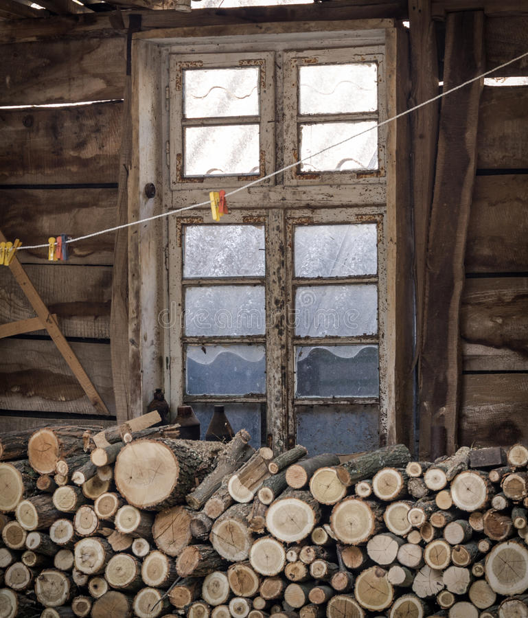 Firewood, rusty window, vignette. A pile of chopped wood, rusty window, vignette stock image