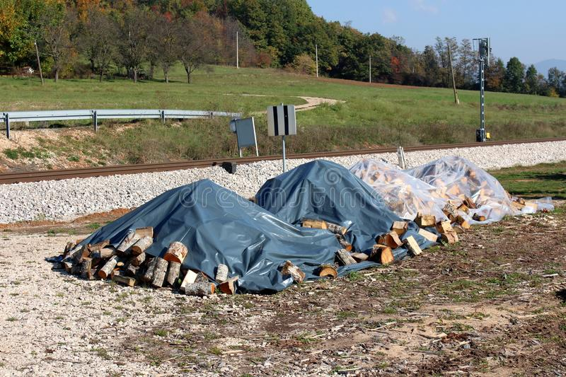 Firewood stacked in four piles covered with nylon protection against rain next to railroad tracks surrounded with grass and trees. On warm sunny day stock photography
