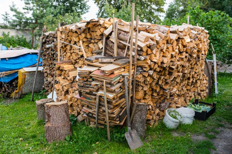 A firewood stacked in a pile, cut trunks. lying behind the house. stock images