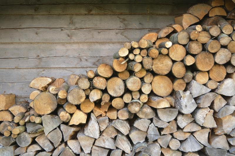 Firewoods stacked at the rustic wooden wall stock photography