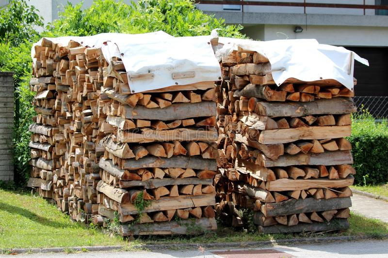 Firewood stacked in two rows in front of family house prepared for cold winter surrounded with grass and paved sidewalk. On warm sunny summer day royalty free stock photography