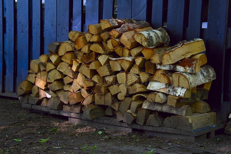 Firewood stacked in woodpile stock image