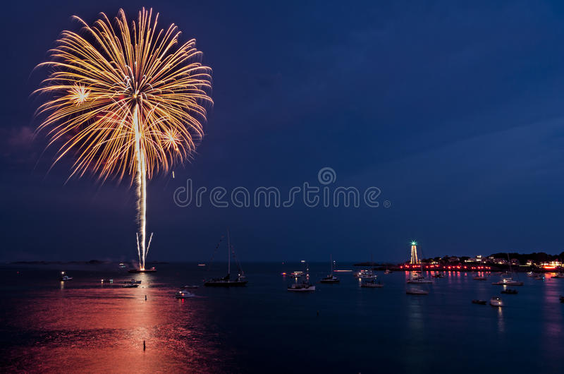 Firework Burst over Marblehead Harbor. Fireworks explode over Marblehead harbor with a lighthouse in the distance stock photos