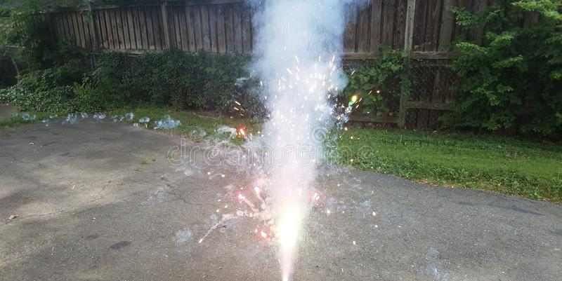 Firework or firecracker and sparks and smoke in driveway royalty free stock images