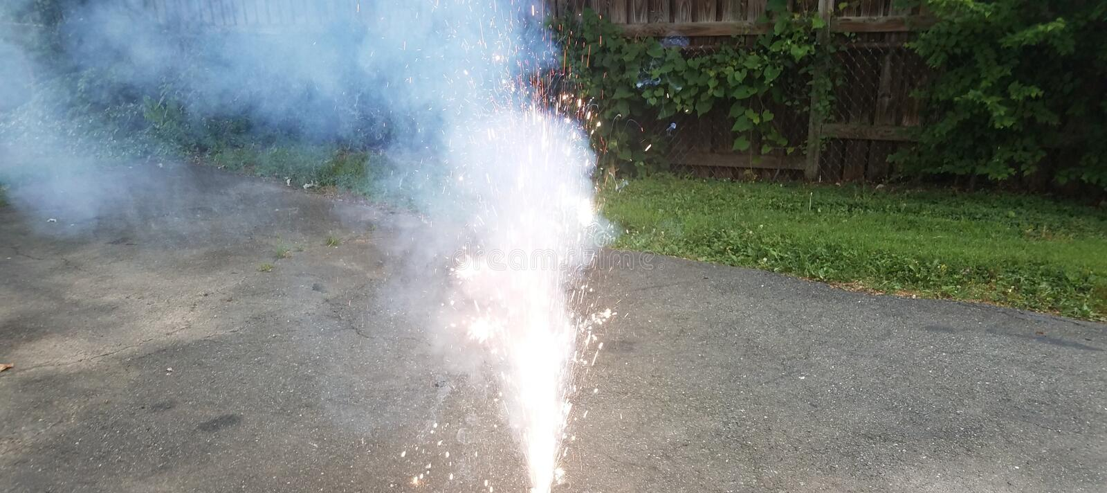 Firework or firecracker and sparks and smoke in driveway stock photo