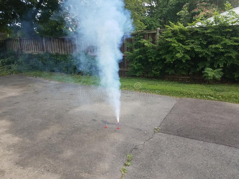 Firework or firecracker and sparks and smoke in driveway royalty free stock photography