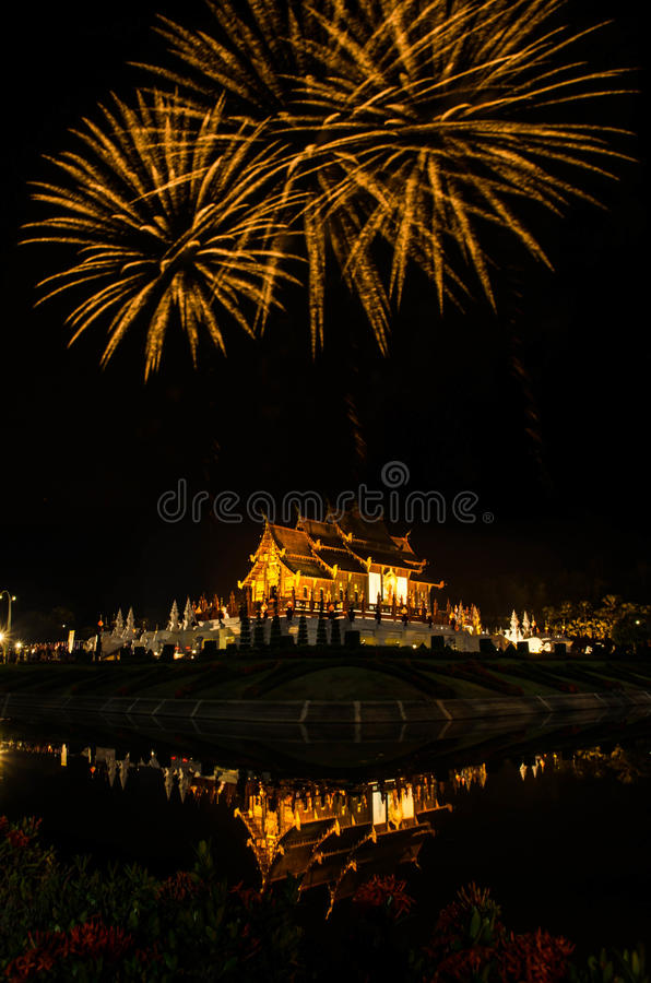 Firework Ho kham luang northern thai style building in Royal Flora temple ratchaphreukin Chiang Mai,Thailand.  royalty free stock photography