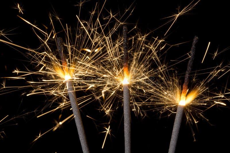 Firework sparklers. Three burning gold firework sparklers emitting sparks against a black background stock photography