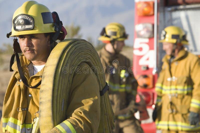 Fireworker, das Firehose auf seiner Schulter trägt lizenzfreie stockfotografie