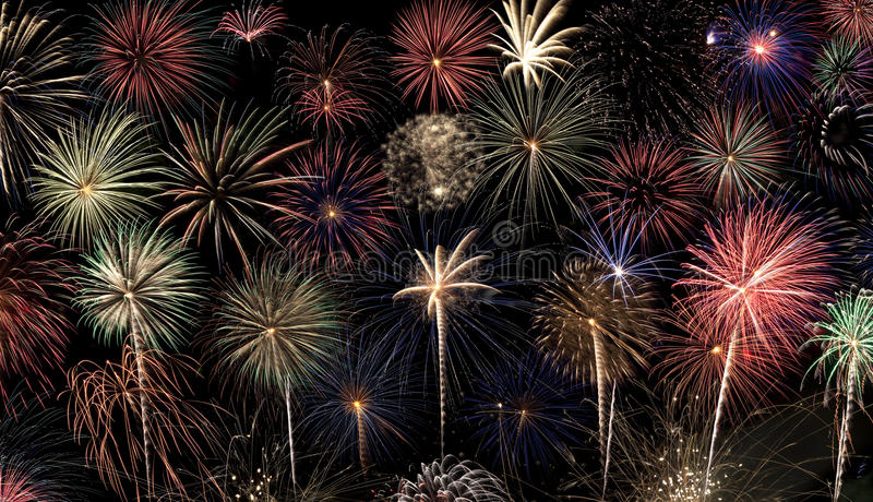 Fireworks Background. A slew of different colored fireworks bursts against a black background stock photo