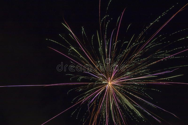 Fireworks on a black canvas. Light trails from a fireworks explosive blast illuminating the black sky long exposure of a firework display on a holiday royalty free stock photo