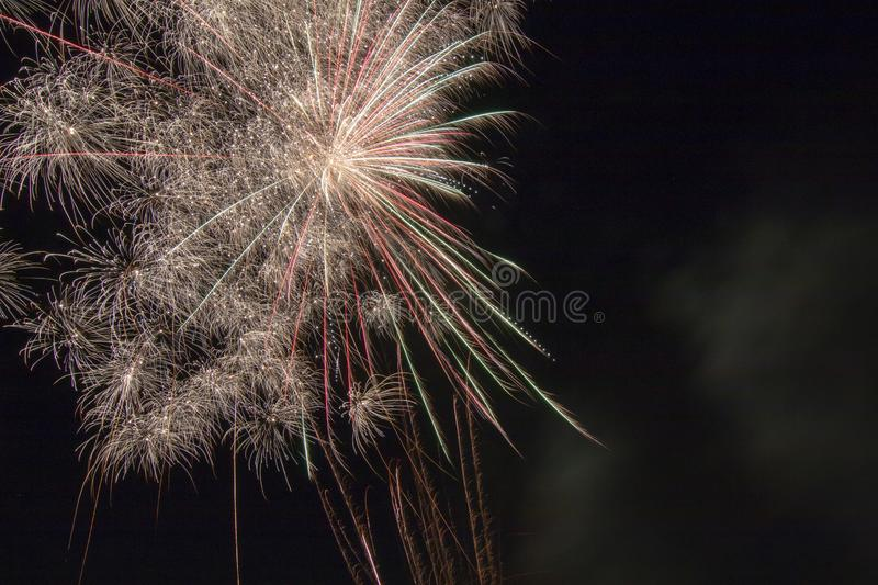 Fireworks on a black canvas. Light trails from a fireworks explosive blast illuminating the black sky long exposure of a firework display on a holiday royalty free stock image