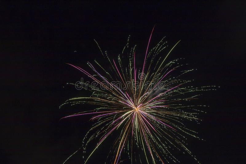 Fireworks on a black canvas. Light trails from a fireworks explosive blast illuminating the black sky long exposure of a firework display on a holiday stock photography