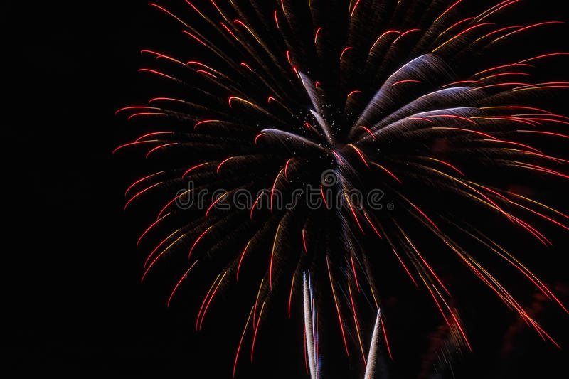 Fireworks on the black sky background. Red colorful holiday fireworks on the black sky background stock images