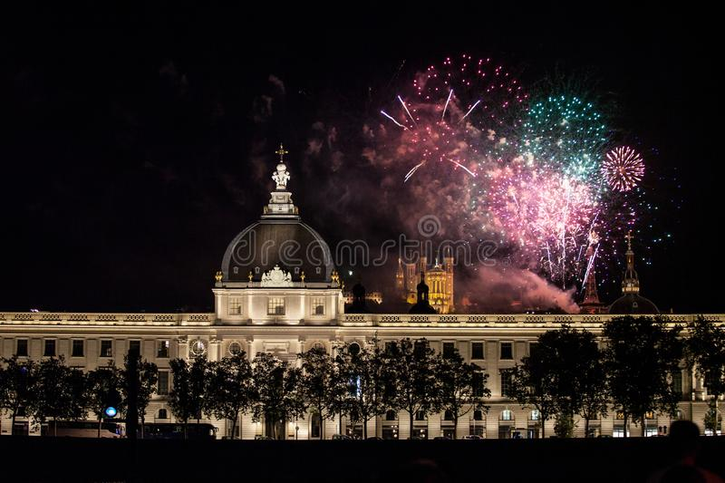 Fireworks bursting over Hotel Dieu in Lyon for French National Holiday, Bastille day, while Basilique de Fourviere Basilica church royalty free stock photo