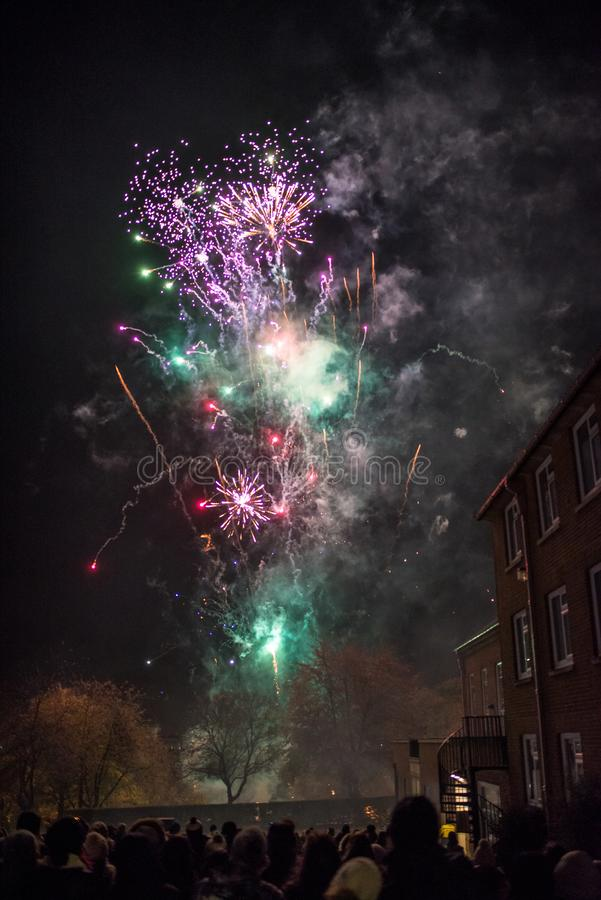 Fireworks with crowd of spectators. A selection of brightly coloured fireworks explode in the nights sky above a crowd of spectators on bonfire night royalty free stock photo