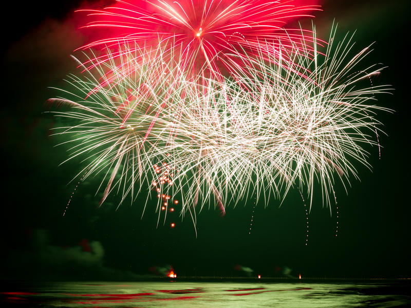 Fireworks explosion reflecting in the water of the sea. Fireworks explosion creates green, red, and white reflection in the water during International Fireworks stock image