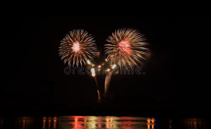 Fireworks festive celebration light show at night over the water. royalty free stock photos