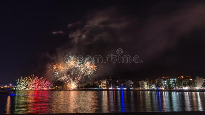 Fireworks, fire castle in the seaside, reflection on the sea at night in Roses , Catalonia, Spain. Fireworks, fire castle celebration in the seaside, reflection stock photography