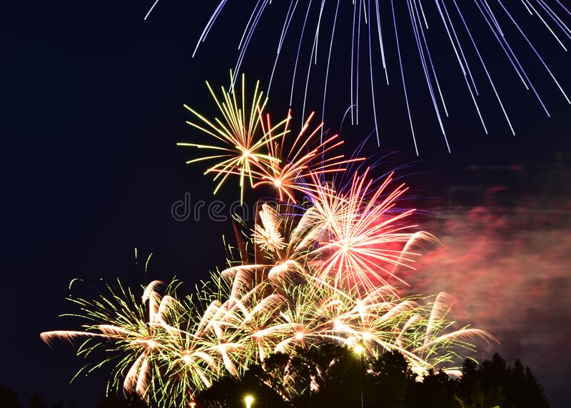 Fireworks illuminate night sky on independence day. Vibrant colors of fireworks display light up night sky on independence day stock photography