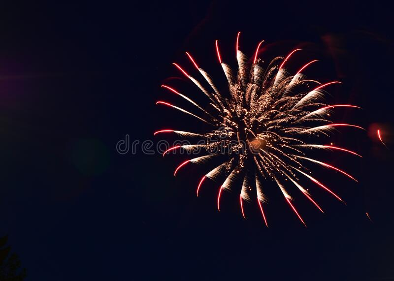 Fireworks illuminate night sky on independence day. Vibrant colors of fireworks display light up night sky on independence day stock photo