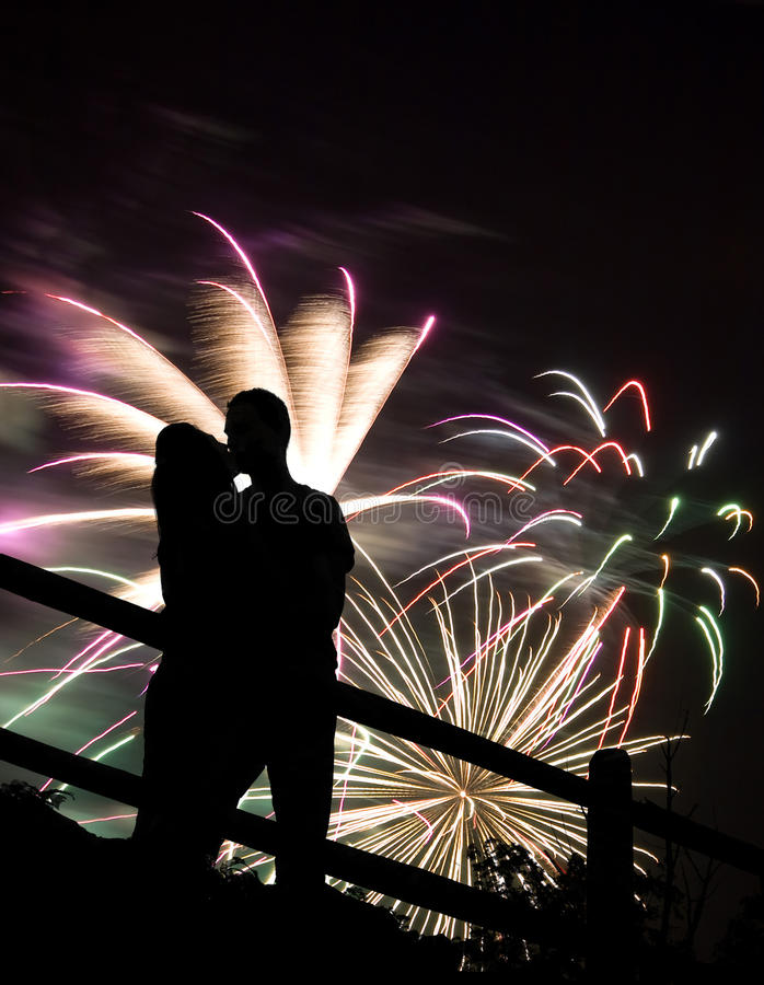 Fireworks Kiss. A silhouette of a kissing couple in front of a huge fireworks display stock photography